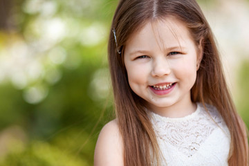 Beautiful smiling little girl in cream dress, against green of summer park