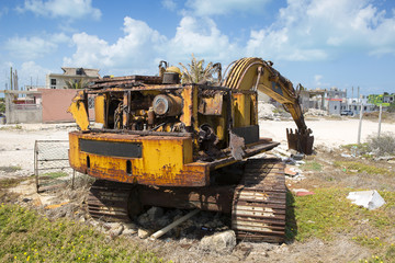 Abandoned excavator outside the city on a sunny day. Fully damaged metal and motor. Rusty surface, ecological waste on the ground.