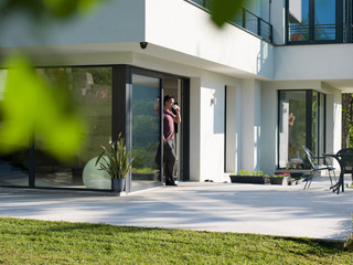 man drinking coffee in front of her luxury home villa