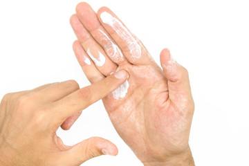 Man applying moisturizer cream on hands, dry skin