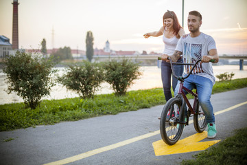 Young couple skateboarding and cycling together