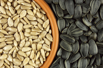 Sunflower seeds in dish on wooden background