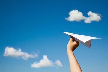 Paper plane in child hand.