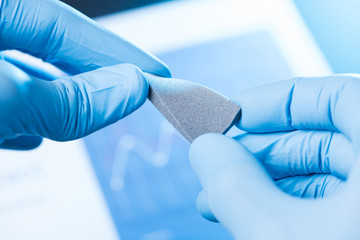 Scientist hand in gloves hold and bend small piece of gray porous foam, new type of material with different properties research concept
