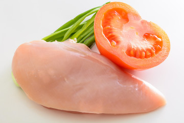 Raw chicken fillet with ripe tomato and green onion. Ingredients for healthy meal