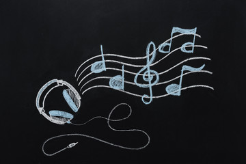 headphones with wire and musical notes drawn on black chalkboard