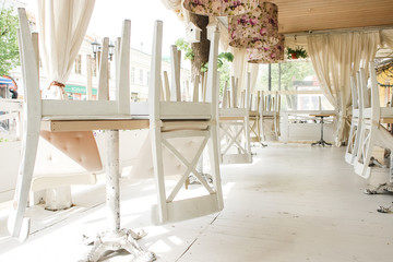 White chairs on tables upside down on street cafe summer terrace.
