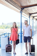 Happy caucasian couple wearing casual summer dress walking with the suitcases through the train station. Taken during sunny summer day.