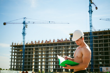 Young sexy male bodybuilder athlete with a bare torso. Manager engineer builder in white protective helmet stands on background of construction of building and construction cranes with documentation