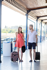 Earnes, smileless caucasian couple wearing summer casual dress walking with the suitcases through the train station. Photo taken at summer daytime.