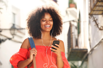 Close up happy woman outside on street with headphones and smart phone