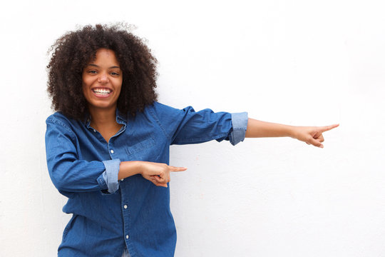 Happy young woman smiling and pointing against white background