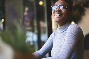 Cheerful american student in trendy eyewear enjoying having fun in coffee shop resting on break,happy prosperous businesswoman satisfied with successful project sitting near blurred advertising area