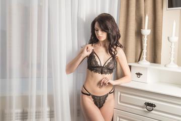 Elegant girl in black lace panties in the room