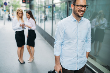 Portrait of handsome young businessman on street