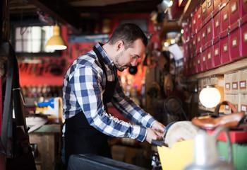Male worker polishing buckle for belt