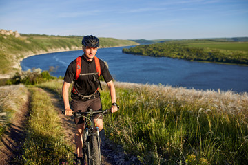 Attractive cyclist riding the mountain bike on the summer trail above the river.