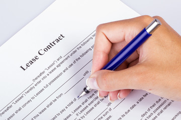Lease Contract Overview - female hand holding a fountain pen going over the contract