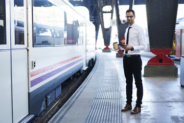 Handsome formally dressed male entrepreneur in eyewear waiting for train on platform enjoying coffee to go, prosperous businessman browsing information about public transport schedule getting to work