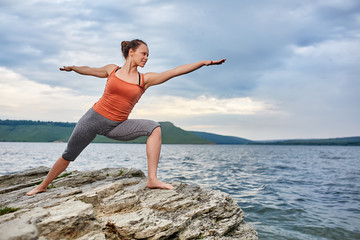 Young woman standing on the stone and practicing yoga near the big river.