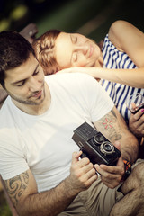 Young man holding camera, girlfriend is sleeping