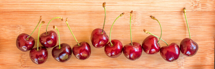 Row of real cherries on wooden background, summer fruit  panorama