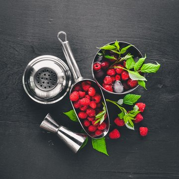 Cocktail of fresh raspberries with ice, on a wooden background. Top view. Free space.