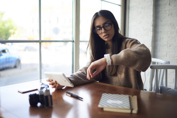 Concentrated female journalist in trendy spectacles checking time on watch while waiting for meeting in coffee shop chatting in social networks using modern touchpad connected to wireless internet