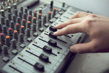Expert adjusting audio mixing console