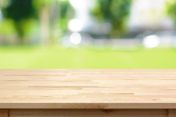 Wood table top on blurred green yard background