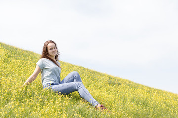 Young girl teenager on a lawn field with yellow flowers. Long chestnut hair. Sunshine, springtime, blue sky. Coloring and processing photos with soft selective focus. Shallow depth of field.