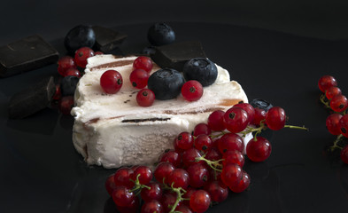 Ice cream with dark chocolate, blueberries and red currants on black background