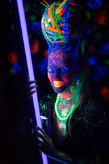 luminous portrait of a girl in the UV rays on dark background