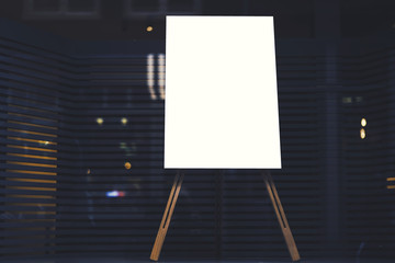 White stylish chalkboard with mock up copy space are for your text message or advertising promotional content, empty presentation wooden board standing on the glass storefront