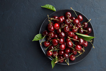 Ripe sweet cherry in black plate on dark stone background.