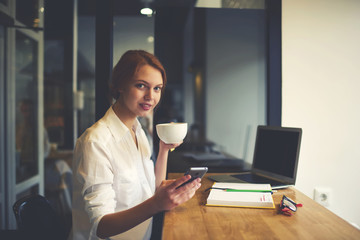 Portrait of charming young journalist having work break enjoying coffee and chatting in social networks sitting in cafe, business woman resting while doing remote job using modern technology