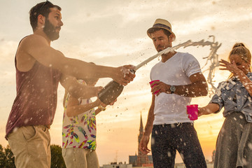 Young man spraying champagne on friends at rooftop party