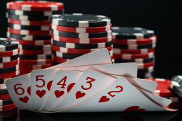 Straight flush against a black background, behind a big bet on winning