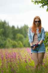 A red-haired girl is standing on a flower clearing