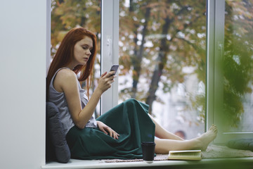 Female red-head hipster girl browsing internet websites and writing mail on cellular device with 4G connection relaxing in comfortable coworking interior with favourite book sitting on windowsill