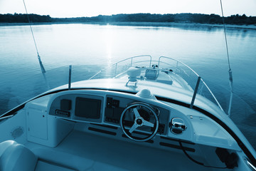 Luxury modern yacht looking over the dashboard of a yacht at sunset.