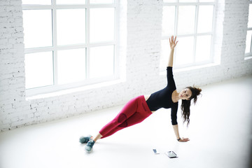 Professional fitness instructor doing static exercises training strength on white promotional background with copy space for advertising, young athletic girl having aerobic workout session indoors