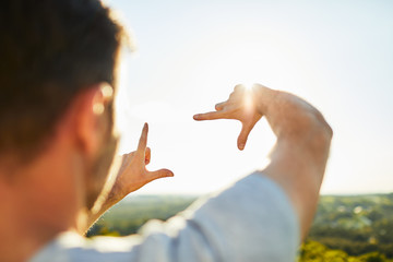 Close-up of man making hands frame gesture to capture the landscape