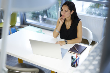 Pensive attractive brunette business woman thinking about organization working schedule while sitting at desktop with laptop computer, professional administrative manager planning startup project