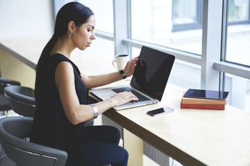 Confident professional journalist dressed in formal outfit making research for project analyzing information from network, attractive concentrated businesswoman typing on laptop computer in office