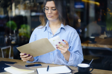 Concentrated attractive business woman in trendy eyewear opening envelope with copy space for advertising checking financial papers, administrative manager receiving letter on mail sitting in cafe