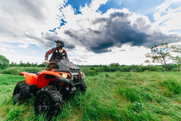 Man on the ATV Quad Bike in a field. Blue sky with clouds.
