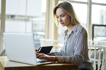 Pensive blonde female journalist doing remote job working on freelance creating article for publication, elegantly dressed businesswoman making financial researchers using laptop computer and wifi
