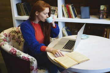 Attractive teenager drinking tasty coffee while looking at laptop screen.Creative charming student enjoying break with aroma coffee while preparing for upcoming examination sitting in cafeteria