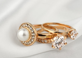 jewelry rings with diamonds and pearl on white cloth, soft focus